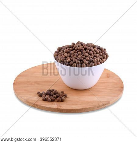 Allspice In White Bowl On Wood Board Isolated On White Background, Copy Space.
