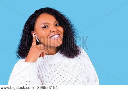 African American Woman Isolated On Blue Background In Studio Listen Music With Earpods
