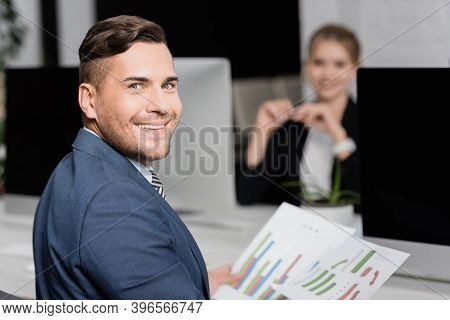 Businessman With Paper Sheets Looking At Camera, While Sitting At Workplace With Blurred Co-worker O