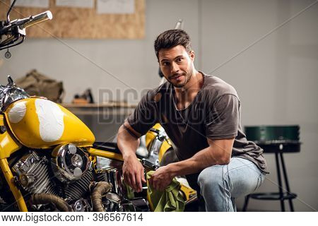 A Handsome Young Motorcyclist In Jeans And A T-shirt Poses For A Photo Sitting On A Bike In His Gara