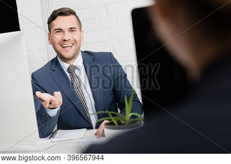 Executive Gesturing, While Sitting At Workplace With Blurred Female Co-worker On Foreground