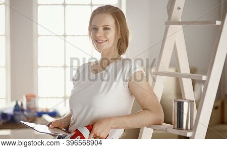 Beautiful Young Woman On A White Wooden Stepladder. Ready To Repair The Room. Women Housework Concep
