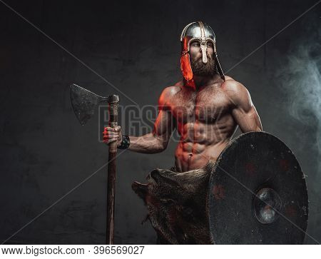 Handsome And Brutal Viking With Beard And Naked Torso With Helmet On Him Posing Staying With Axe And