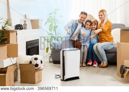 Air Purifier In Living Room With Happy Family Moving To New Apartment