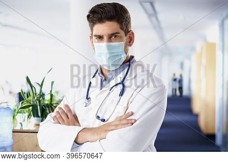 Male Doctor Portrait While Standing With Arms Crossed In The Hospital's Foyer