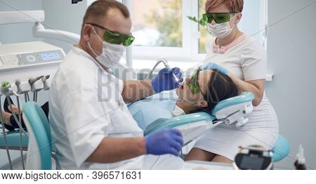 Doctor Dentist Treats Teeth Of A Beautiful Young Girl Patient. The Girl On Reception At The Dentist.