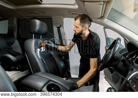 Car Detailing Concept. Brush Cleaning Of The Car Interior, Front Seat. Caucasian Young Man In Black