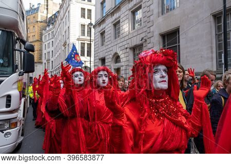 London, Uk - October 18, 2019: A Row Of Extinction Rebellion Red Brigade Protesters Parading In Lond