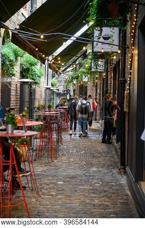 London - September 30, 2019: Portrait Shot Along A Pretty Cobbled Alley With An Outdoor Dining Area