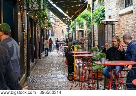 London - September 30, 2019: View Along A Pretty Cobbled Alley With An Outdoor Dining Area At Camden