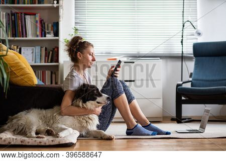 woman with dog at home and laptop