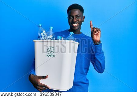 Young african american man holding recycling wastebasket with plastic bottles surprised with an idea or question pointing finger with happy face, number one