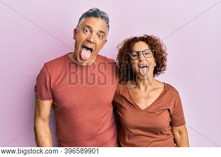 Beautiful middle age couple together wearing casual clothes sticking tongue out happy with funny expression. emotion concept.