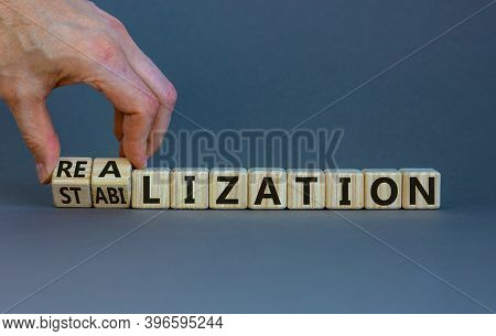 From Realization To Stabilization. Hand Turns Cubes And Changes The Word 'stabilization' To 'realiza