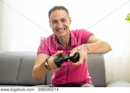 Young Excited Man At Home Sitting On Living Room Sofa Playing Video Games Using Remote Control Joyst
