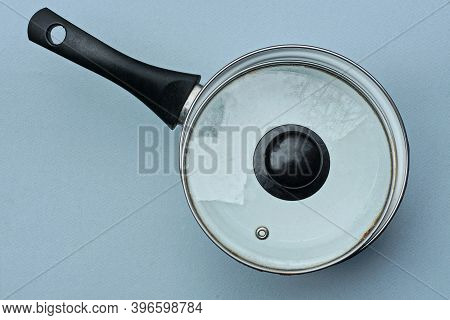 One White Black Enameled Pan Covered With A Glass Lid Stands On A Gray Table