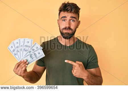 Young hispanic man holding dollars puffing cheeks with funny face. mouth inflated with air, catching air.