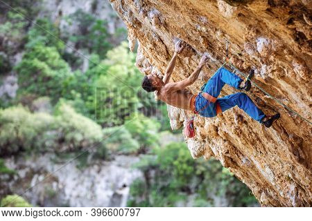 Rock Climber On Overhanging Cliff. Caucasian Male Climber Gripping Small Handholds On Challenging Ro
