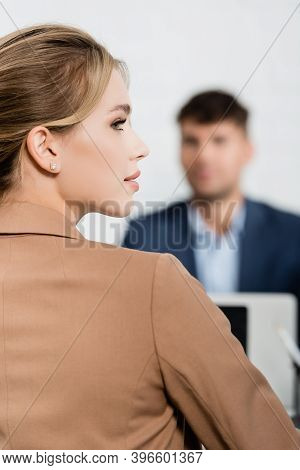 Back View Of Businesswoman Looking Away With Blurred Co-worker On Background