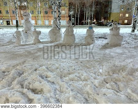 A Group Of Various Snow Covered Snowmen. With Snowdrifts In Front, Trampled By Various Traces. On A