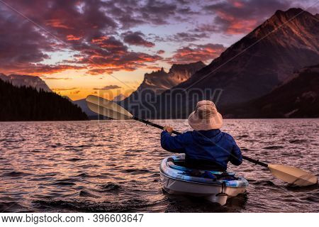 Adventurous Man Kayaking In Glacier Lake Surrounded By The Beautiful Canadian Rocky Mountains During