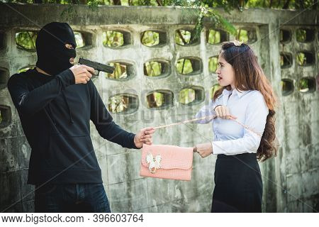 The Robber Is Robbing The Female With A Gun, Pointing The Gun To The Face