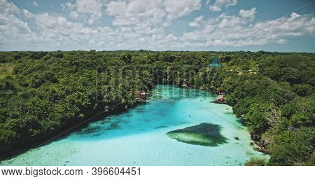 Weekuri limpid lake with salt water at tropical green forest. Turquoise saltwater lagoon at tropic plants. Relax and serene summer scenery of Sumba Island landmark, Indonesia, Asia at soft light