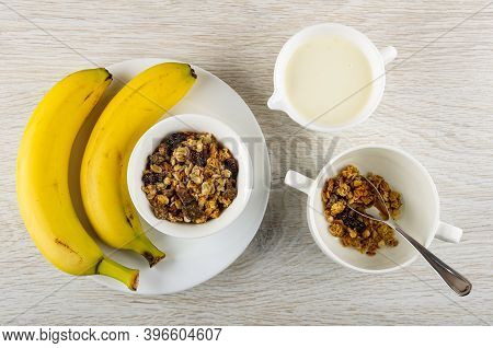 Two Bananas, Bowl With Baked Muesli In Plate, Pitcher With Yogurt, Teaspoon In White Bowl With Grano