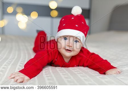 Closeup Portrait Of Newborn Baby. Cute Caucasian Baby Girl 3-4 Months Old In Santa Costume Lying On