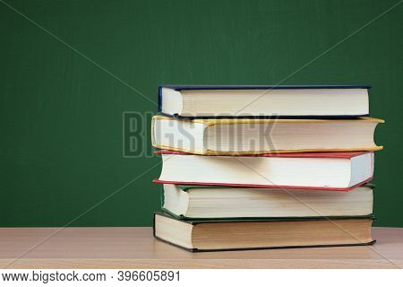 Books. A Stack Of Textbooks On The Table On A Green Background. School, Education.