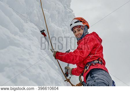 Alpinist Woman With Ice Tools Axe In Orange Helmet Climbing A L