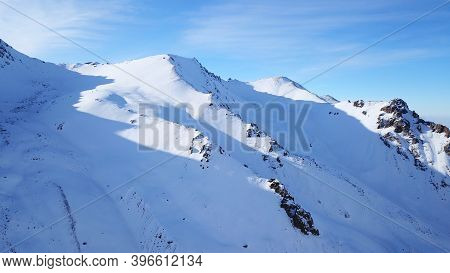 Snow Mountain Peaks With Rocks. View From Drone. In Places, You Can See Glaciers, Large Rocks And Ro