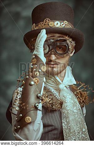 Fantasy world, scientific inventions. Portrait of a handsome victorian steampunk man on a grunge background.