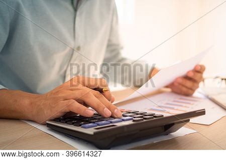 Business People Sit At The Desk Using A Calculator To Calculate The Profit-loss Figures Shown In The