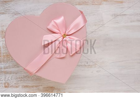 Valentine's Day Holiday.pink Heart Box With Bow On A Light Shabby Chic Background. Blank Postcard.lo