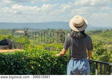 Asian Woman Wear Weave Hat And Stand On Wooden Terrace. She Feeling Relax And Happiness. She Look At