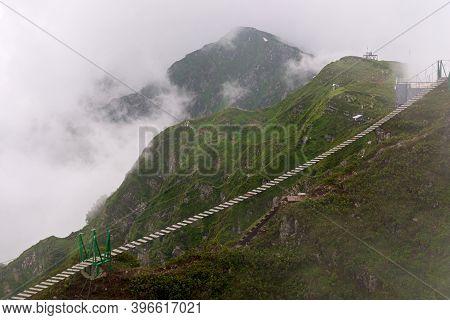 Hanging Bridge Over Chasm In Fog. Rope Bridge Between Peaks In Cloud.