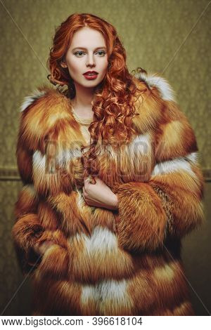 Beautiful young woman with red hair poses in a luxurious fox fur coat on a golden vintage background. Winter beauty fashion. Fur coat style.