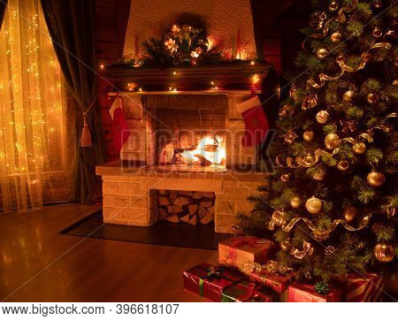 Christmas decorated tree in dark interior with fireplace and window