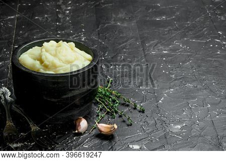 Mashed Potatoes In A Bowl With Garlic And Thyme. On Black Rustic Background.