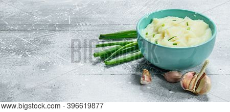 Mashed Potatoes With Green Onions And Garlic. On A Rustic Background.