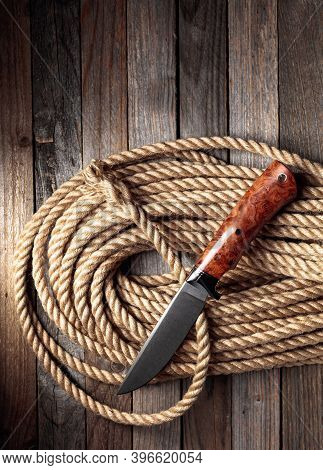 Hunter Combat Hand Made Knife And Hemp Rope On Wooden Background. The Blade Has A Beautiful Damask P