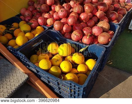 Crates Of Fresh Oranges And Pomegranates In The Bright Sun At The Market