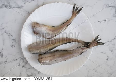 Pollock Fish Chilled Without A Head Is On A Plate