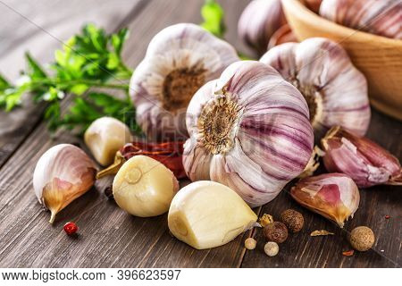 Closeup Of Garlic Bulbs On Wooden Table With Garlics Blur Background.a Set Of Fresh Garlic On The Ch