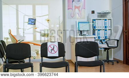 Dental Clinic Reception With Nobody In It Modern Equipped With Signs On Chairs For Social Distance D
