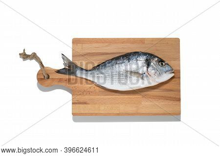 Isolated Fresh Dorade Gifthead Fish On The Wooden Cutting Board