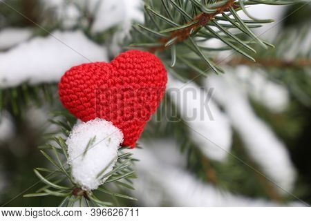 Christmas Heart, Red Knitted Symbol Of Love On Fir Branches Covered By Snow. Background For Romantic