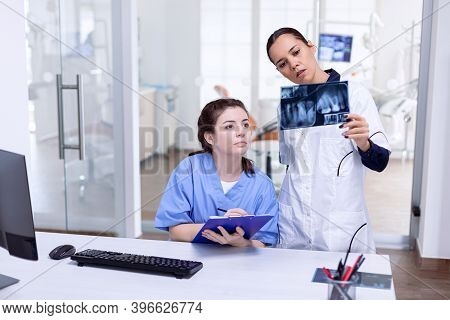 Dentist Holding Teeth X-ray Explaning Diagnosis For Nurse At Reception. Stomatolog And Her Assistant
