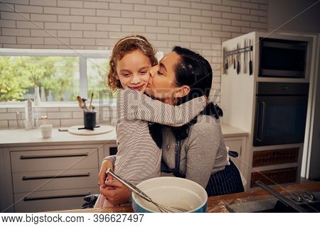 Loving Mother Embracing Daughter And Kissing Her On Cheek While Preparing Meal On Kitchen Counter